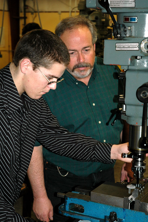 Instructor Paul Eastwood works with a student in the Machine Tool Technology lab