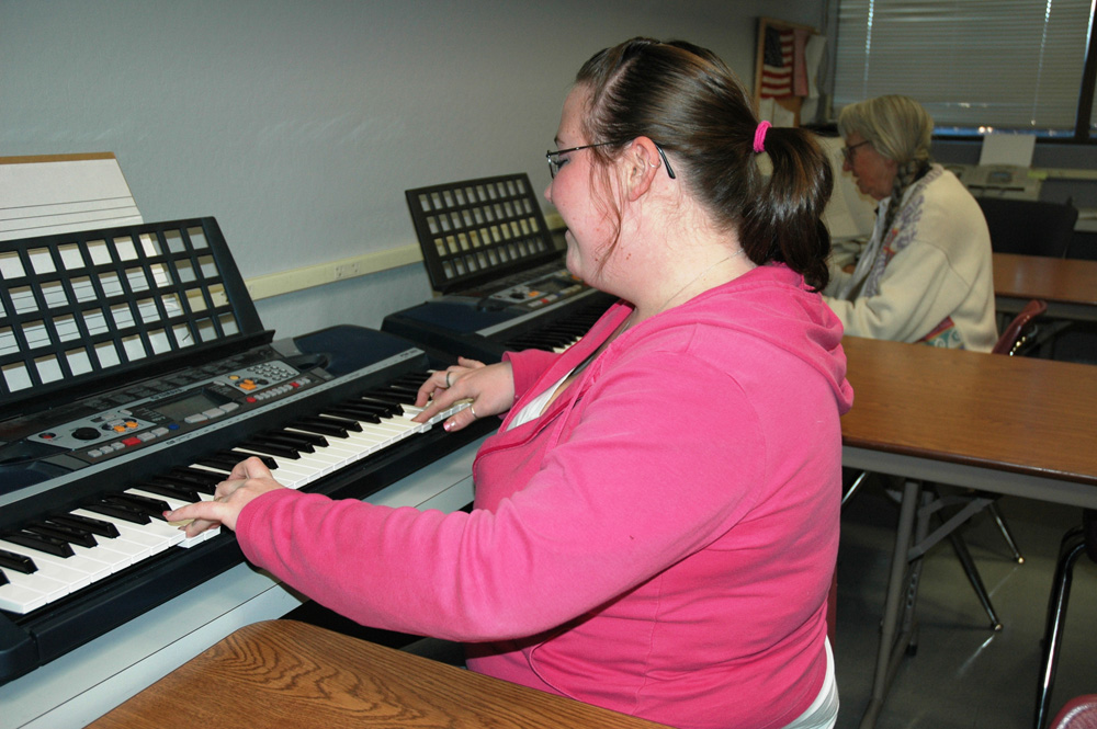 Students in a piano class take beginning music lessons.
