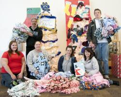 WNC students sit amid the blankets they made for children through the Linus Project.