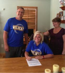 Carlee Beck signs with WNC as her parents look on.
