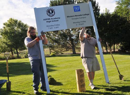 Sign Pro employees install the new ASPIRE Academy/WNC sign at the Douglas campus.