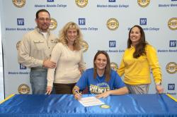 Lauren Knorzer signs an athletics letter of intent, as her parents and Coach Leah Wentworth look on.