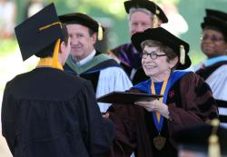 Western Nevada College President Carol Lucey presents a diploma on Monday.