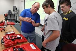 Construction Instructor Robert Ford demonstrates a laser level to students.