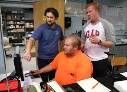 Physics Professor Tom Herring working with students Kyle Hollingshead and Timothy Hoover.