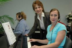 Stephanie Arrigotti (center) works with a student in the piano lab